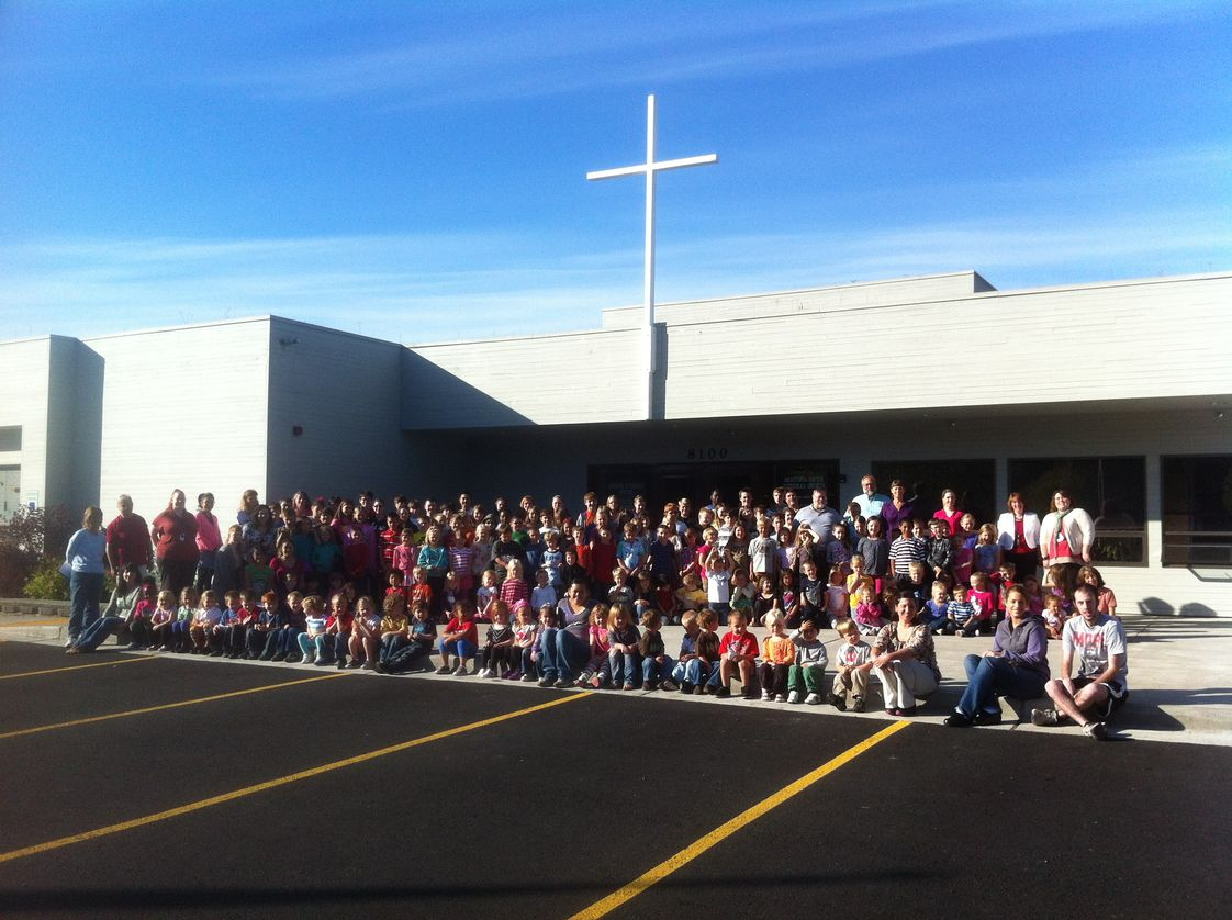 Anchor Lutheran School Photo - Students and staff in front of the main entrance of our school, with the cross of Christ lifted above. In our whole program, Jesus is lifted up as the example we follow and the purpose to which we commit ourselves.