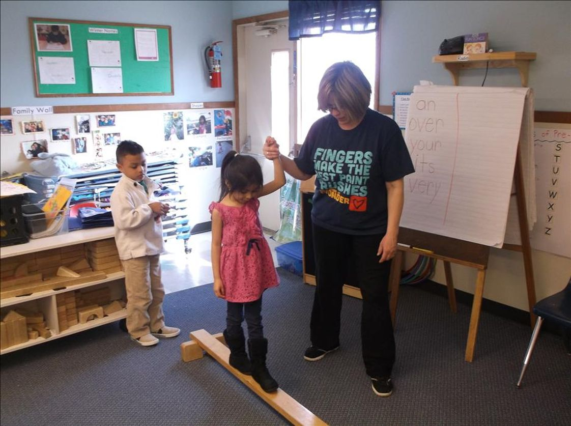 Bensenville KinderCare Photo - Walking with Ms. Arlene on the balance beam, great gross motor fun!