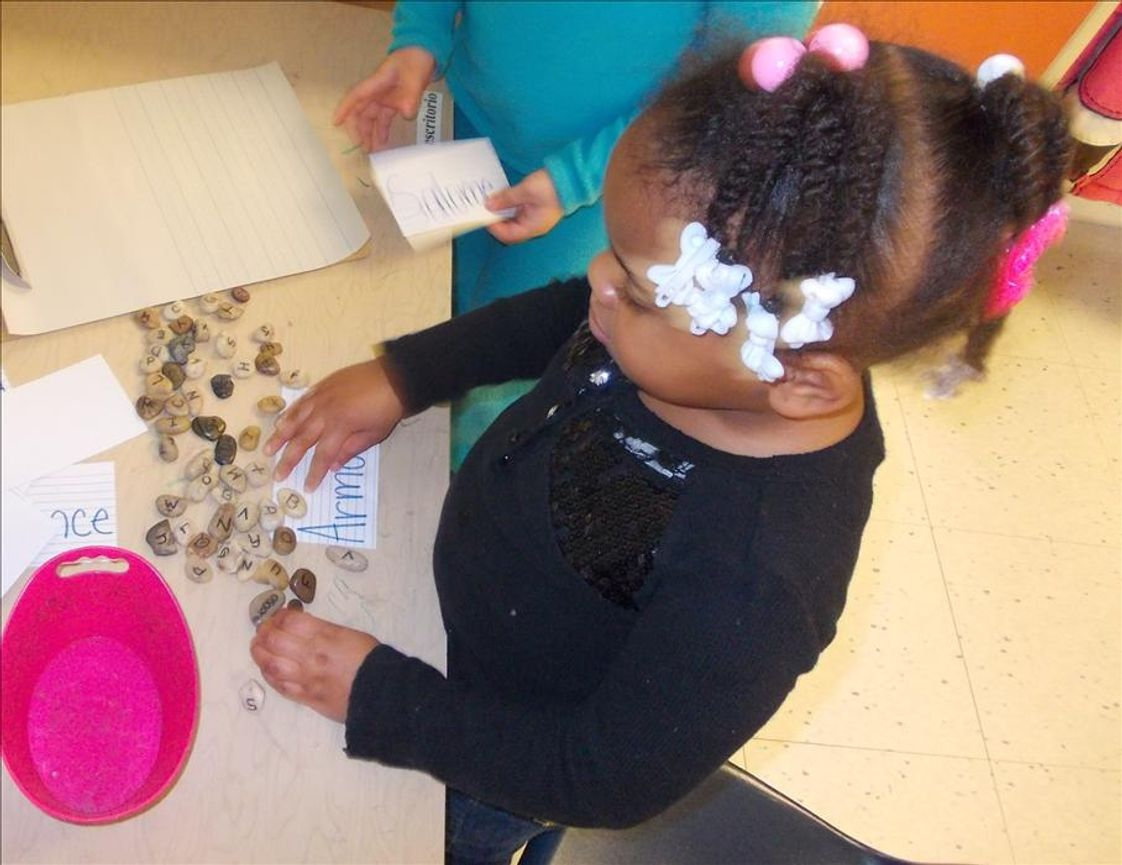 Whitcomb KinderCare Photo #1 - Our Juniour Kindergartners stepped back into time during our Dinosaur unit! Here, a child enjoys writing her name in stones in our prehistoric writing center!