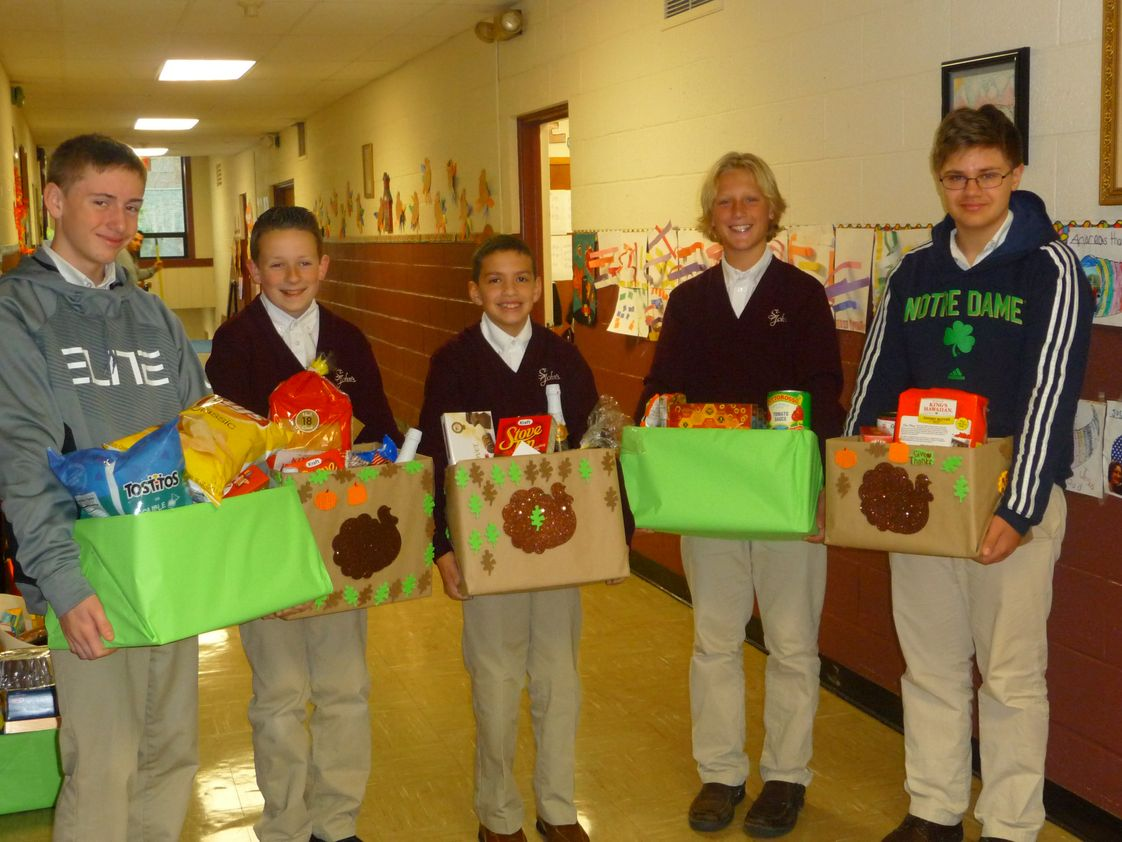 St John School Photo - Grade 8 boys help with some of the Thanksgiving baskets that were collected for needy families for House on the Hill in Goshen.