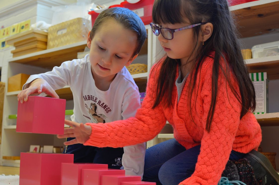 Gladwyne Montessori Photo - 3rd year primary student gives a lesson to a 2nd year primary student using the iconic pink tower, specifically designed for children to learn about space, size, and comparison in a concrete manner.