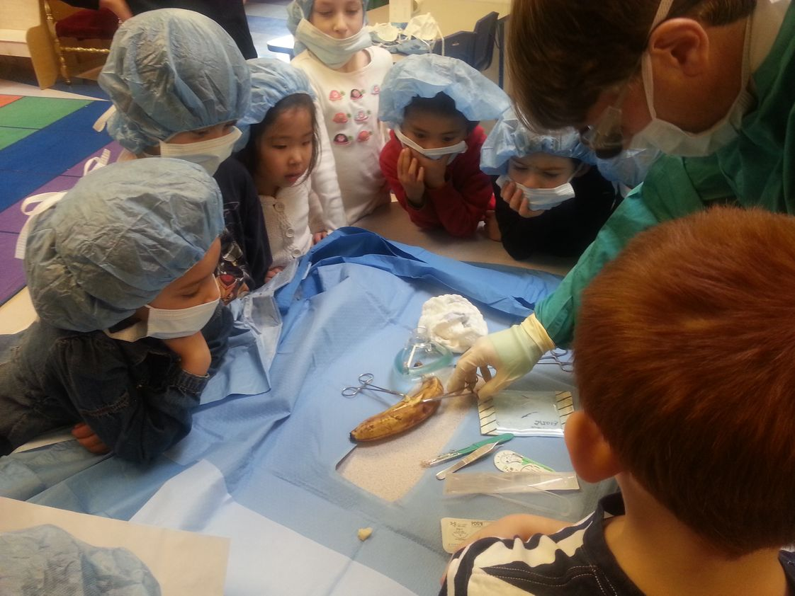 Emerson School Photo #1 - Kindergarten students learn how surgeons work by watching one operate on a banana in their classroom.