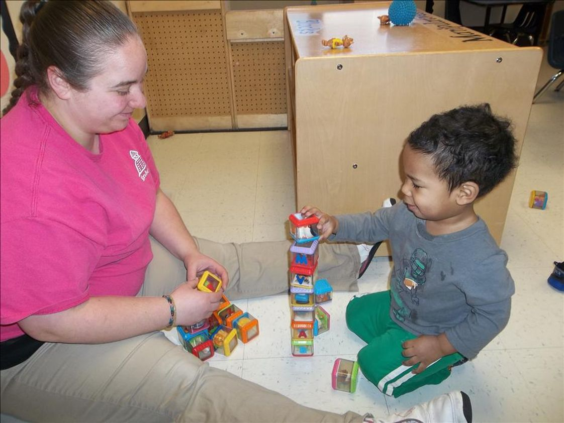 Highland KinderCare Photo - Stacking blocks with his teacher.