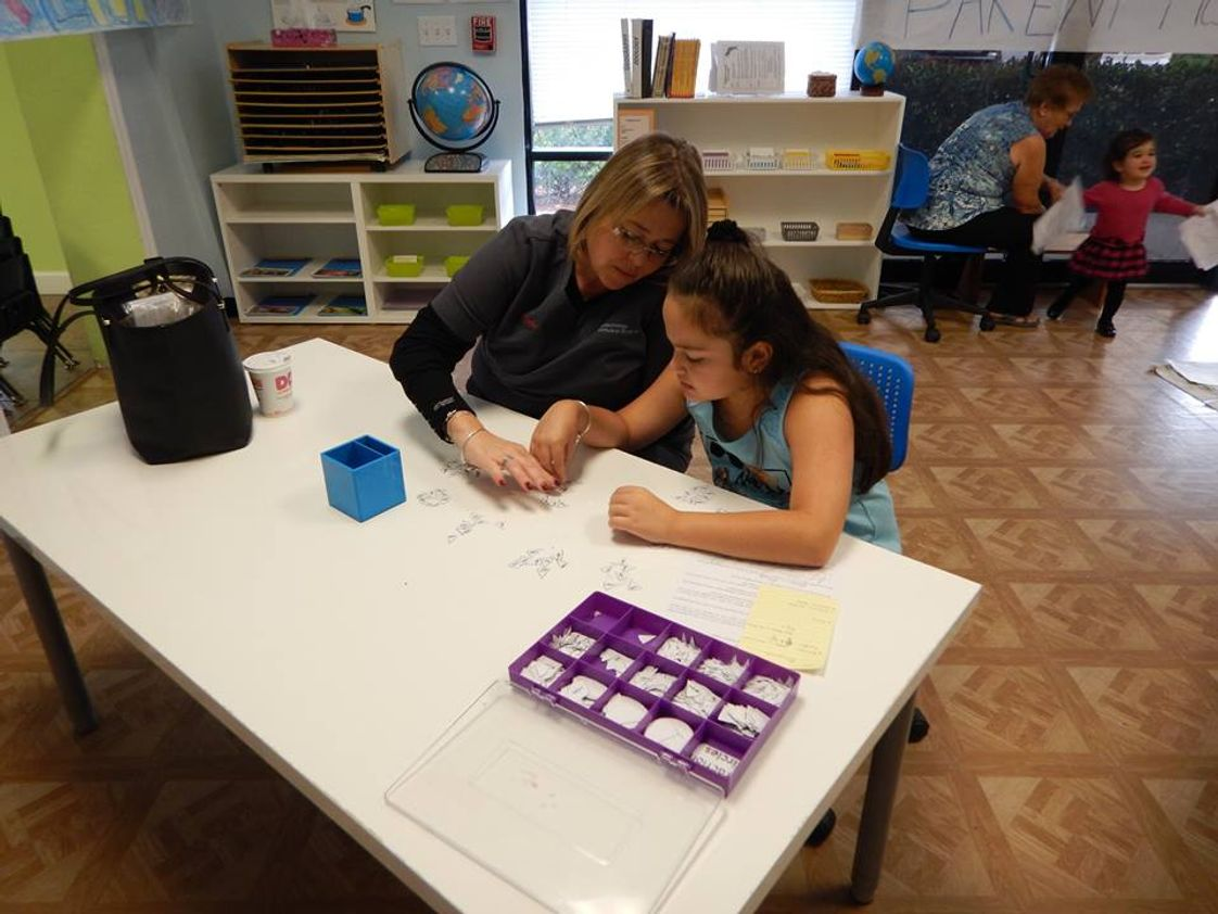 Waves Of Wonder Montessori School Photo - Parent Night is a wonderful opportunity for students to show off their hard work to their families. Here you see one of our Upper Elementary students working with her mother on her lesson.