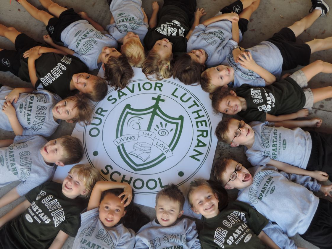 Our Savior Lutheran School Photo - Our Savior's Kindergartners around the crest that represents the strengths from which our school is founded.