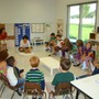 "Montessori School Of Westminster Photo #2 - Students in one of our Primary classes (for ages 3 through kindergarten level) meet at the ""ellipse"" to observe their directress explain the use of classroom materials."