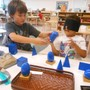 Montessori De Terra Linda Photo - Two Lower Elementary (ages 6-9) students work together to explore the geometric solids.